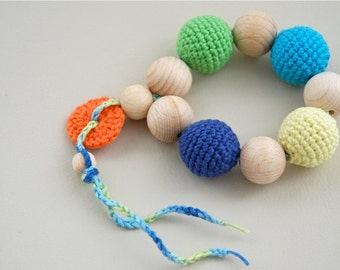 Teething toy with crochet wooden beads. Light blue, green, yellow, blue, orange.