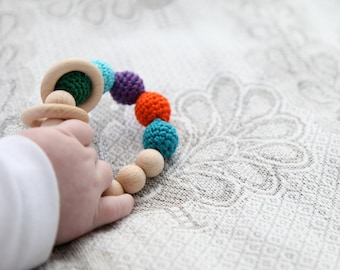 Peacock rattle. Teething ring toy with crochet wooden beads. Bright orange, blue, smaragd  green, violet, teal, cyan..
