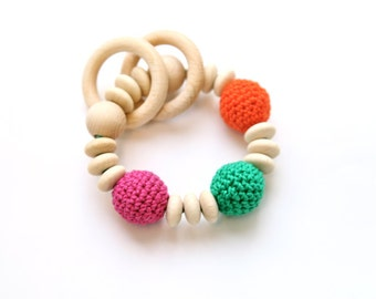 Teething toy with crochet wooden beads and 2 wooden rings. Pink, green, orange wooden beads rattle. Nursing bracelet.