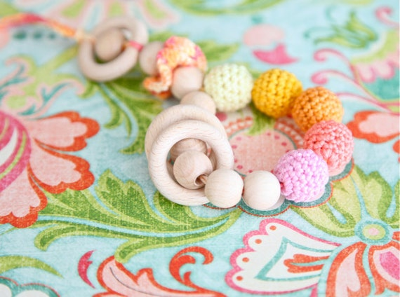 Teething toy rattle with crochet wooden beads and 3 wooden rings. Yellow, orange, coral, pink.