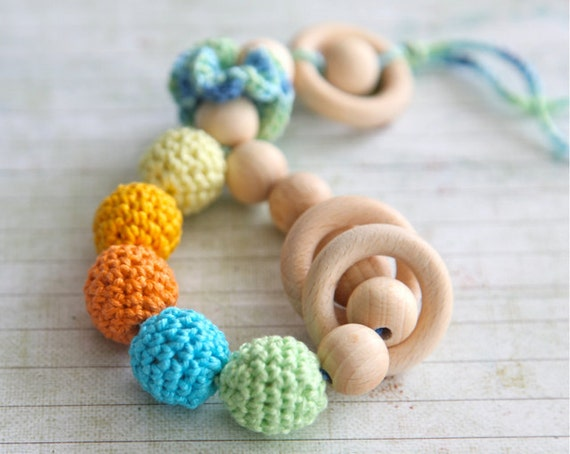 Teething toy rattle with crochet wooden beads and 3 wooden rings. Yellow, orange, light green, aqua blue/ cyan.