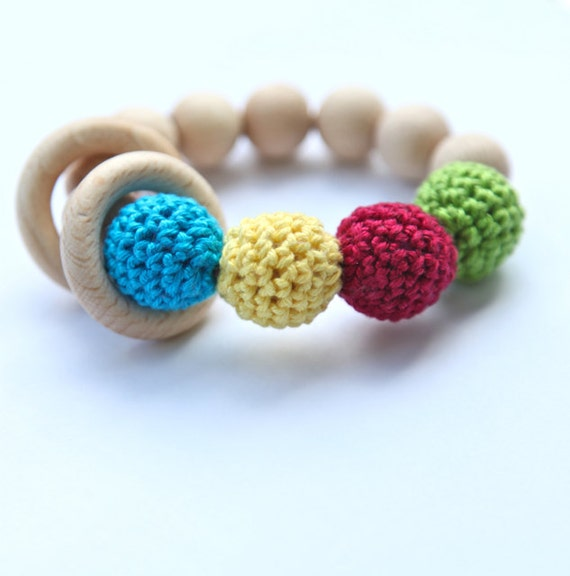 Neon blue, bright green, cherry red, yellow teething ring toy with crochet wooden beads. Rattle for baby.