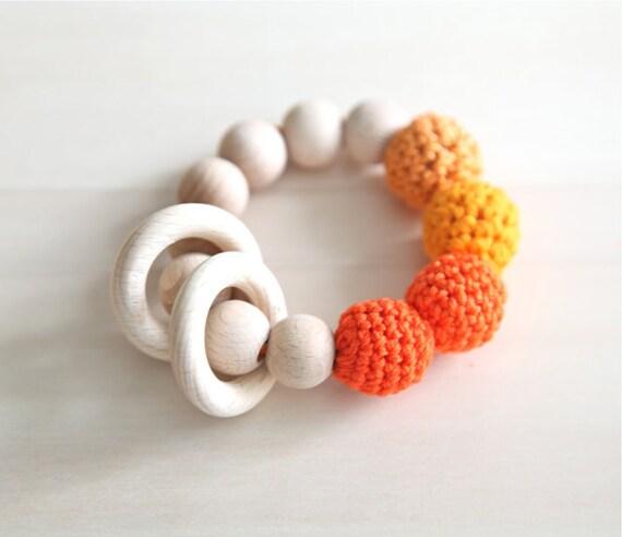 Orange, tangerine, pumpkin, deep carrot orange teething ring toy with crochet wooden beads. Rattle for baby.