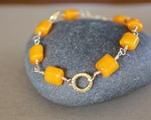Orange glass bead and gold wire wrapped bracelet with Om charm.