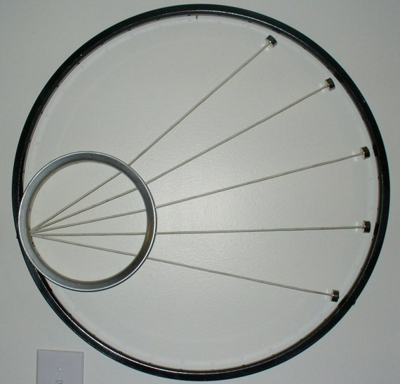 Kinetic sculpture with magnets, string and bicycle rims