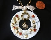 Large washer pendant with hand stamped images and gold accents.