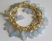 Glass leaf and pearl wraparound bracelet on knotted gold leather cord.