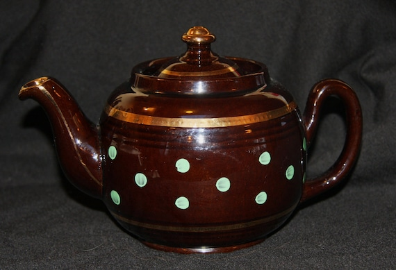 Little vintage brown teapot with green polka dots