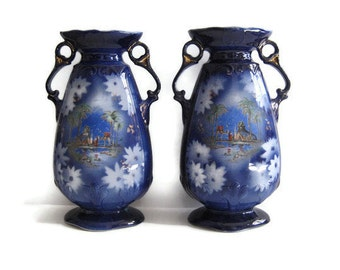 Pair of vintage flow blue vases with desert scene and gold trim