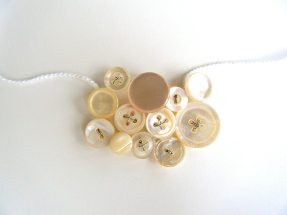 White button necklace.  Wire wrapped vintage button collage on a crocheted white necklace with ball and loop enclosure