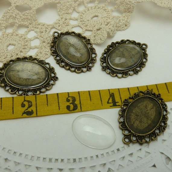 4 fancy edged oval aged bronze / brass bezels with 4 clear glass cabochons 37 mm x 28.5 mm