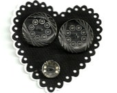 Two large clear glass buttons with a design cut  and one small clear button.