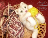 Needlefelted white kitty playing with a knitting wool