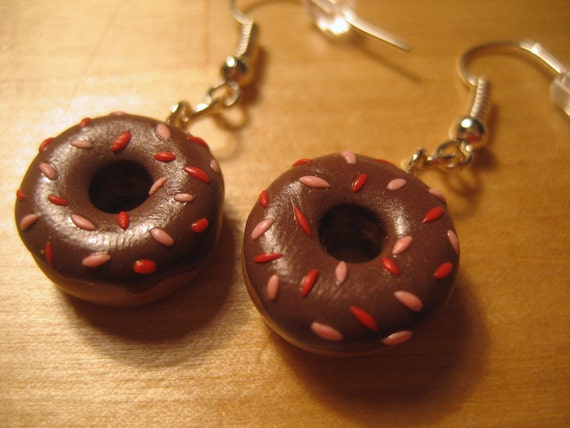 Chocolate donut earrings with red and pink sprinkles made from polymer clay.