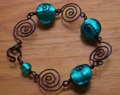 Handmade black wire wrapped spiral and teal blue foil glass bracelet