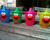 5 Elmo sippy cups in  pink yellow or green