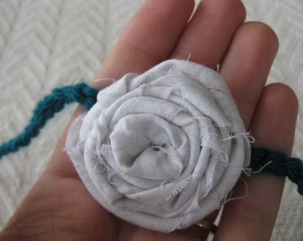 White rolled fabric rosette on thin teal crochet headband