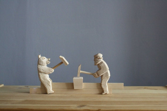 wooden carved moving bear and man beaten with a hammer