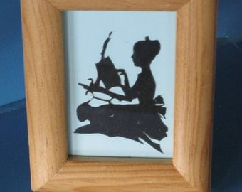 Framed Victorian silhouette of a girl in a hat.