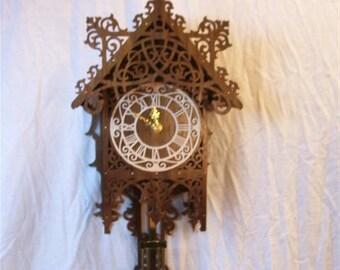 Fretwork pendulum clock made of walnut.