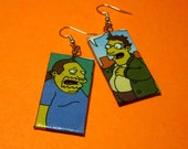On SALE 25% OFF. Simpsons Earrings. Comic Capture. Comic Store Guy and Nerd Doug. Comic Collage. Wood Base. TV Show. Geeks.