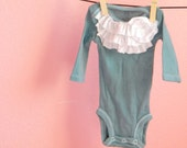 dark teal baby onesie with white ruffles and long sleeves in size nb
