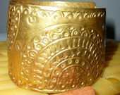 Brass embossed bracelet with open end.