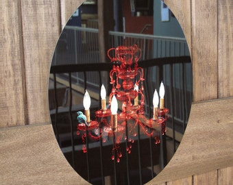 """Crimson Perch--Illustration of a teal bird perched upon a red crystal chandelier Infused onto a 14"""" High Gloss Metal Oval"""