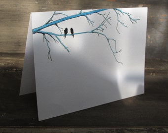 A  greeting card on artist watercolor paper with one of my original illustrations of two black birds perched on blue branches