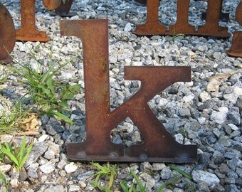 "Lowercase metal letter ""k"" on stand"