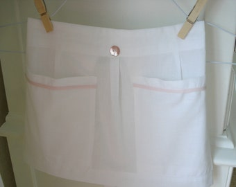 Cotton, white with pale pink trim, half apron pleated, with  pockets and tie closure , baby/toddler