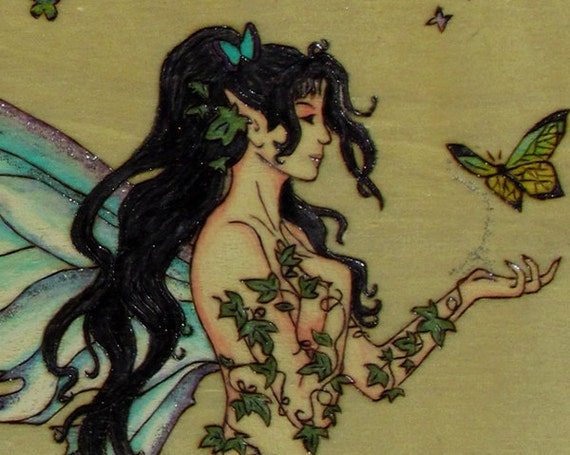 A beautiful wood burning of a fantasy fairy with butterflies on a jewelery/treasure box