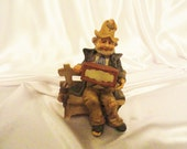 Vintage hobo figurine, plays music box while his monkey looks on, flower in his hat, on park bench