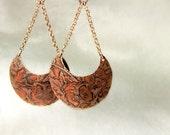 Copper earrings with flower pattern.