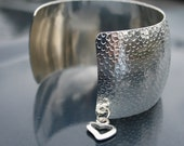 Silver Colored Cuff Bracelet textured and adorned with a cute Open Heart charm