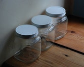 Three matching old fashioned glass storage jars with lids