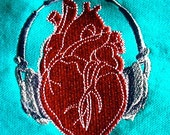 Anatomical Heart wearing Headphones on Organic Full Size Turquoise Napkins.
