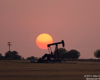 An Orange Sun Sets Behind an Oil Pump in Oklahoma