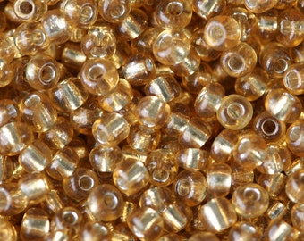 Gold transparent silver lined size 11/0 glass seed beads - 15 grams