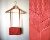 red leather clutch with embossed chevron detailing, shoulder strap and gold hardware