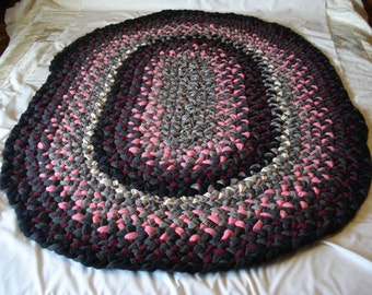 Eye-catching Pink and black oval braided rug