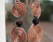 Wire wrapped double spiral copper earrings with red tigereye bead