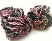 Two skeins of wavy, bulky handspun art yarn in brown, cream, pink and green