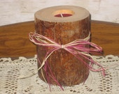 Pine tealight candle holder decorated with wine and tan raffia.
