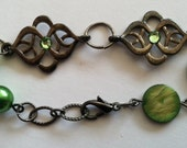 Lime green swarovski elements sparkle on this gunmetal bracelet, finished with lime green flat shell pearls and green swarovski pearls.