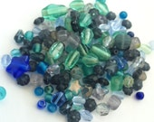 1.5 ounces of glass bead soup in many different shapes and assorted shades of blue and turquoise and teal.