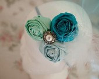 Vintage style shades of aqua handrolled Rosettes with a button and feather embellishment.
