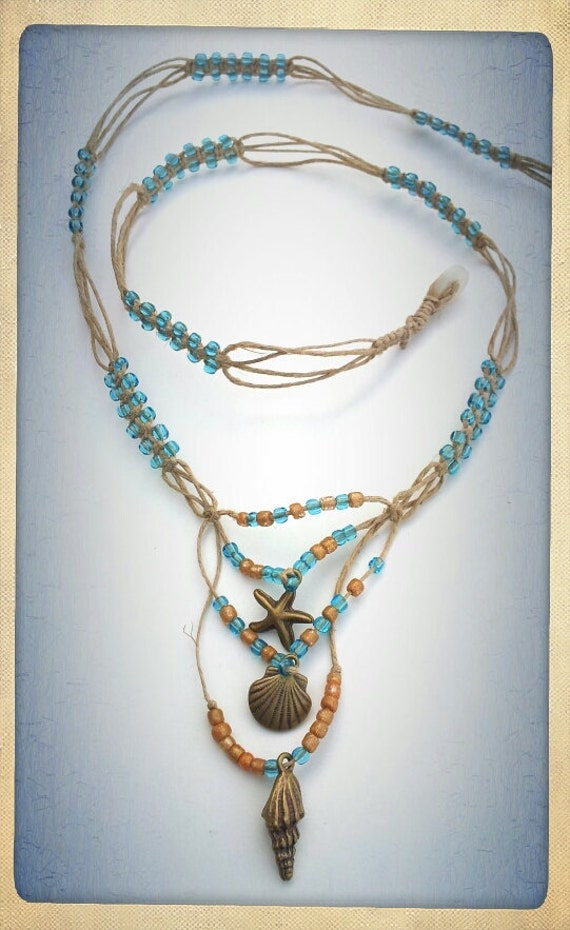 Beautiful long necklace made with hemp featuring seashells and blue beads