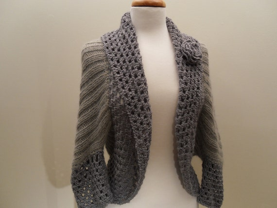 Handknit spring shrug sweater with a wide lace crochet trim and a flower pin