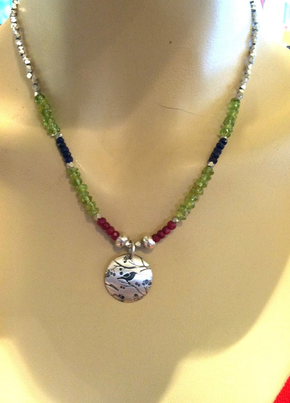 Etched Sterling Sparrow Pendant with peridot, sapphire, and ruby stones.